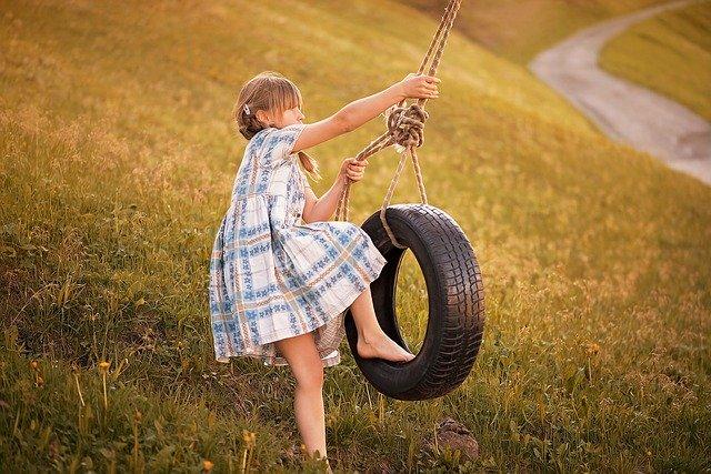 malá holčička houpající se na pneumatice