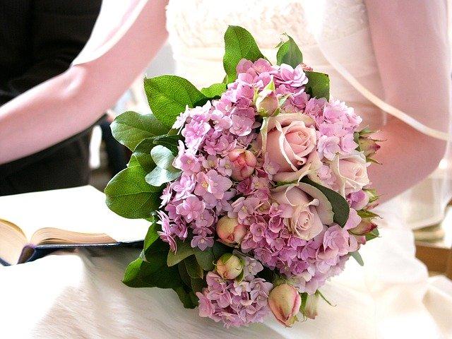 nevěsta drží svatební kytici s růžemi