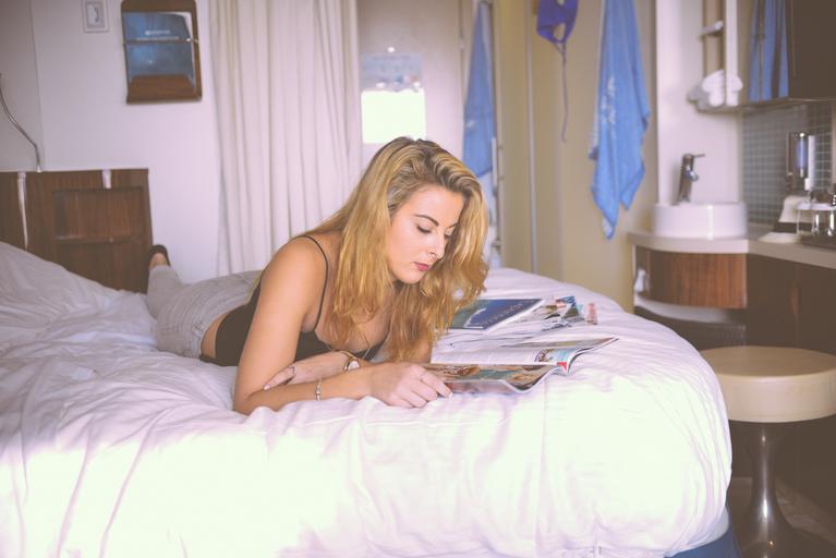 mladá žena si čte v posteli knihu