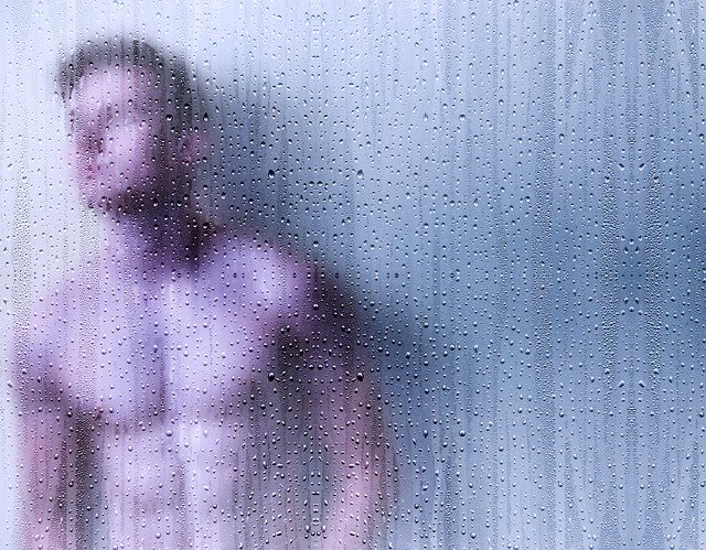 a young man behind a wet glass-curtain in a bathroom